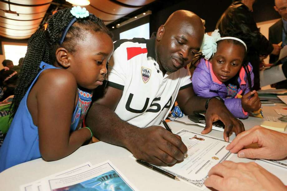 Babatunde Olayande from London sings the Certificate of Citenzenship for his daughter Olayinka Olayande (right), 6, as her sister, Charlotte, 4, looks on during a Children's Citizenship Ceremony at the DoSeum, San Antonio's museum for kids, on Saturday, Jan. 14, 2017.  Fourty-two immigrant children from 21 different countries took the oath to become United States citizens at the ceremony as part of Dream Week events.  MARVIN PFEIFFER/ mpfeiffer@express-news.net Photo: Marvin Pfeiffer, Staff / San Antonio Express-News / Express-News 2017