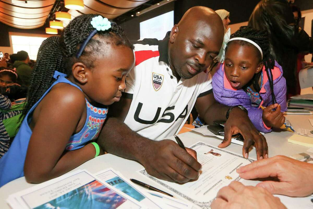 Babatunde Olayande signs a citizenship certificate for daughter Olayinka (right), 6, as sister Charlotte, 4, looks on.