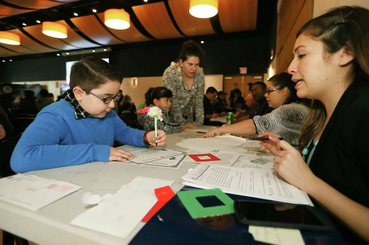 Luis Aguilera Gomez from Eagle Pass signs his Certificate of Citizenship with the help of officer Zaira Timoco with Citizenship and Immigration Services as immigrant children took the oath to become United States citizens in a Children's Citizenship Ceremony at the DoSeum, San Antonio's museum for kids, on Saturday, Jan. 14, 2017. Fourty-two children from 21 different countries became citizens as part of Dream Week events. MARVIN PFEIFFER/ mpfeiffer@express-news.net