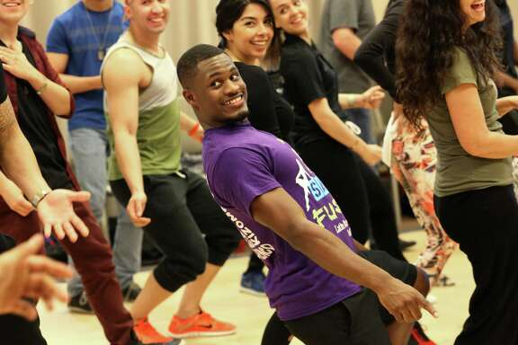 Houston Salsa Congress workshop participant Harrison Bohanan follows instructor Franklin Liranzo's dance moves to warm up before a class Saturday in Houston.