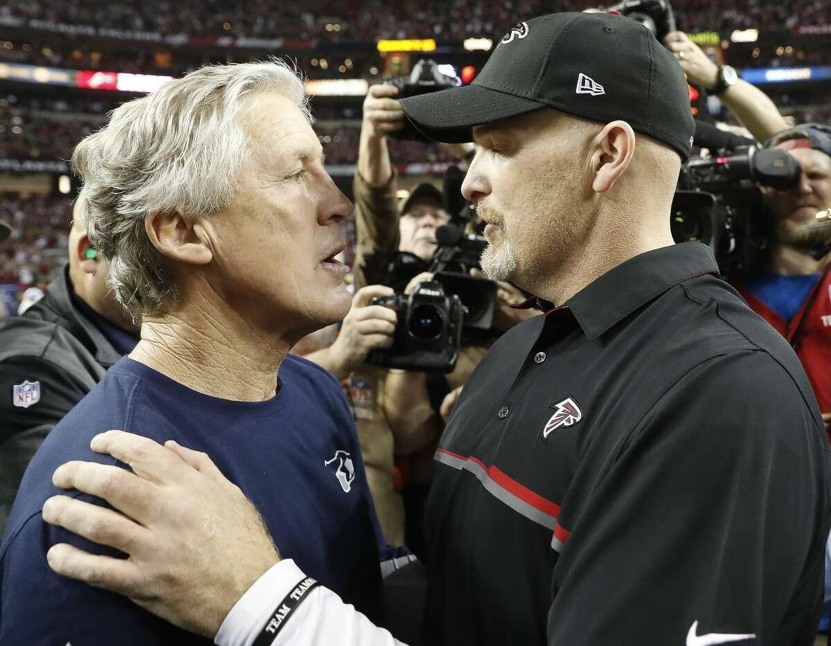 Seahawks head coach Pete Carroll, left, speaks with Atlanta head coach Dan Quinn after the game. The Falcons won 36-20.