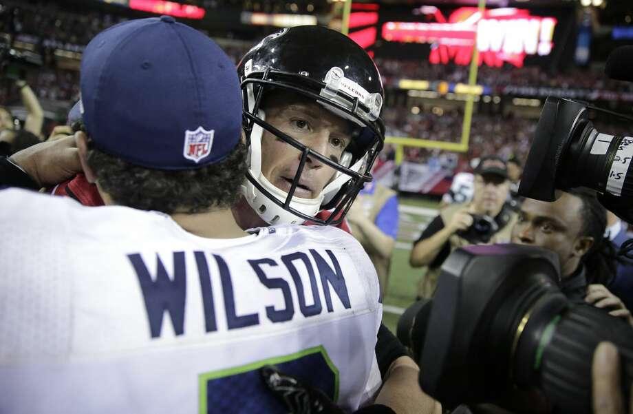 Atlanta quarterback Matt Ryan, right, embraces Seahawks quarterback Russell Wilson after the game. The Falcons won 36-20. Photo: David Goldman/AP