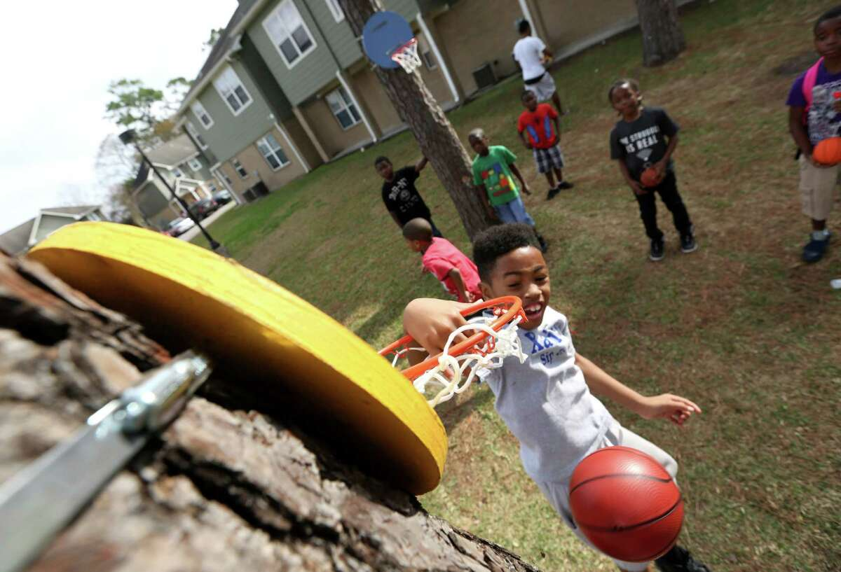 Oxford Place Apartments young resident Jerrell Llorance, 8, dunks the basketball into a newly installed goal. The public housing community gathered Saturday to celebrate the opening of a new, unique play space.