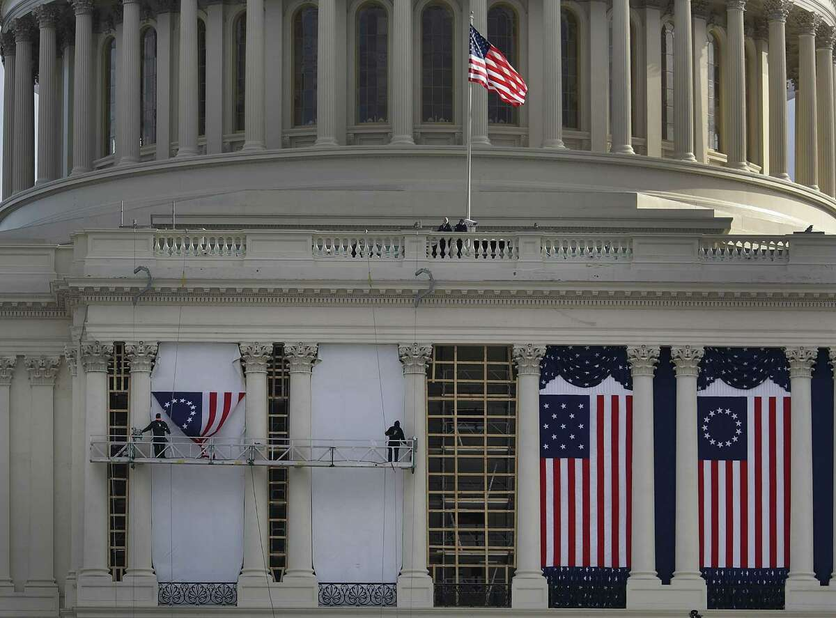 Decorations for the inauguration made by the Dixie Flag and Banner Co. of San Antonio are hung on the front of the Capitol.