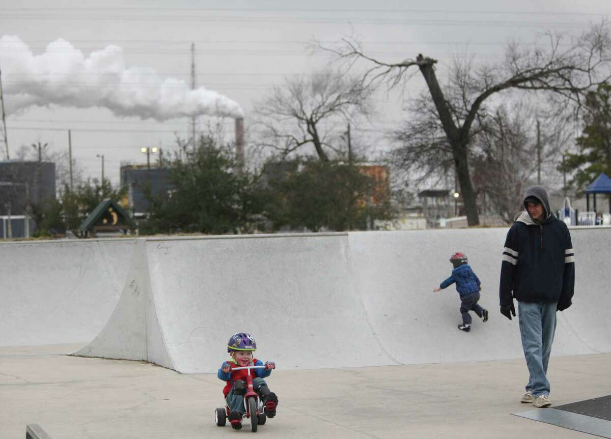 Aaron Smith, of Baytown, looks at his sons Vaughn Smith, 4, and Vance Smith, 2, as they play in the skate park at Unidad Park across the street from Exxon Mobil's Baytown Complex in February 2014. Residents in San Patricio County have compared the Exxon ethane steam cracker complex proposed for their area to the Baytown petrochemical plant.
