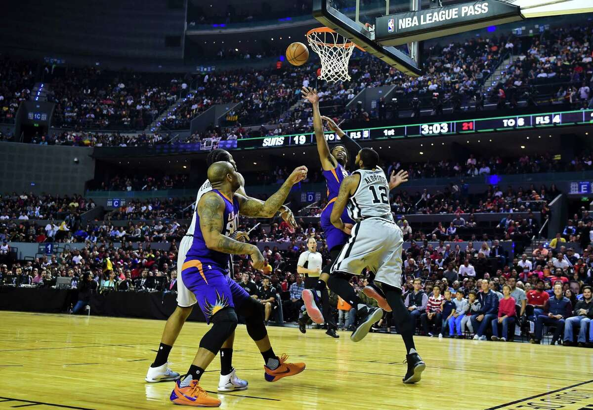 Phoenix Suns' T.J. Warren (C) vies for the ball with San Antonio Spurs´ LaMarcus Aldridge (R), during an NBA Global Games match at the Mexico City Arena, on January 14, 2017, in Mexico City. / AFP PHOTO / RONALDO SCHEMIDTRONALDO SCHEMIDT/AFP/Getty Images