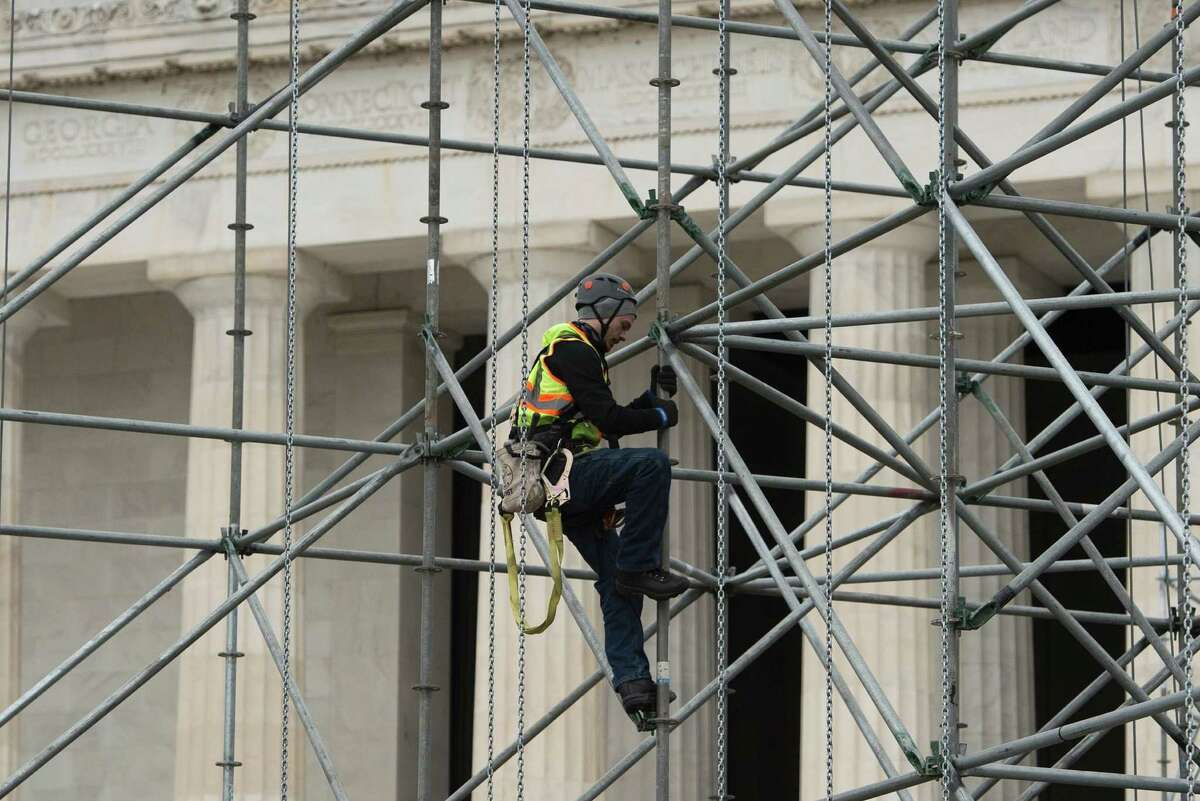 Construction workers climb scaffolding being put up as part of a stage to be used in the presidential inauguration festivities for incoming US President-elect Donald Trump at the Lincoln Memorial in Washington, DC on January 11, 2016. / AFP PHOTO / Andrew CABALLERO-REYNOLDSANDREW CABALLERO-REYNOLDS/AFP/Getty Images