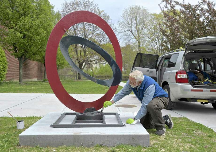 """Artist Murray Bodin does a little touch-up on his sculpture """"Circle VI"""" after it was installed on the lawn of the municipal center in Bethel last spring. This sculpture was part of Bethel Art's first exhibit. (File photo) Photo: H John Voorhees III / Hearst Connecticut Media / The News-Times"""