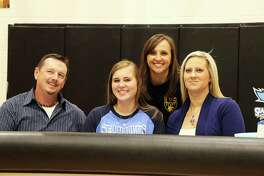 Stepfather Duane Alford, Coach Karen Slack and her mom Heather Frazier join Madisyn Frazier at the signing on Jan. 10 in the gymnasium at Liberty High School.