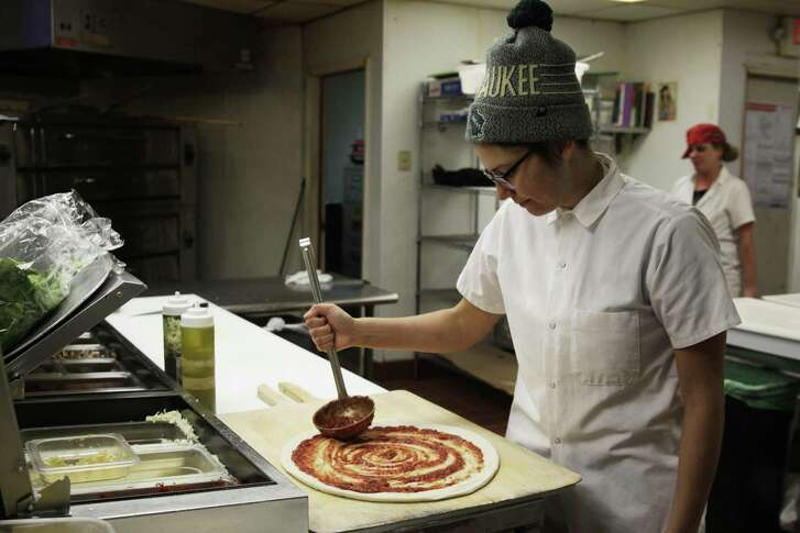 Andrea Ledesma spreads sauce on pizza dough at Classic Slice restaurant in Milwaukee. The 28-year-old has a four-year degree and quit a higher-paying job because it made her miserable. Ledesma thought she would be making more at this point in her life and she's not alone.