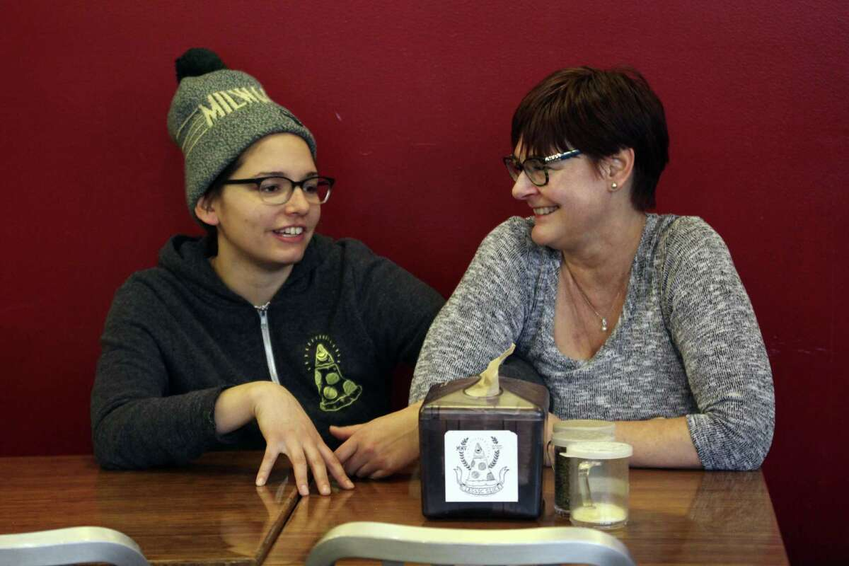 Andrea Ledesma (left) talks with her mother, Cheryl Romanowski, at Classic Slice pizza restaurant, where Ledesma works. Ledesma, 28, says her parents owned a house and were raising kids by her age. Not so for her, even though she has a college degree.