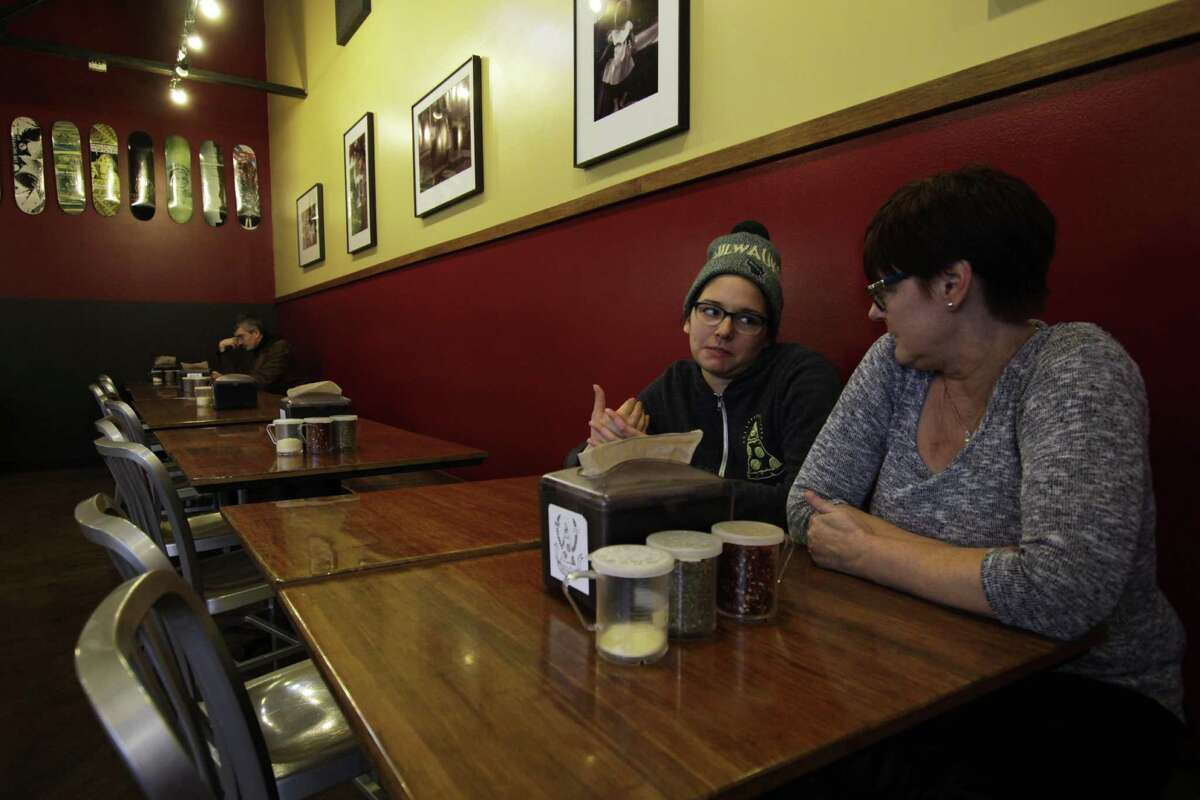 Andrea Ledesma (center) talks with her mother, Cheryl Romanowski, at Classic Slice pizza restaurant, where Ledesma works, in Milwaukee. With a median household income of $40,581, millennials earn 20 percent less than boomers did at the same stage of life, despite being better educated, according to a new analysis of Federal Reserve data by the advocacy group Young Invincibles.