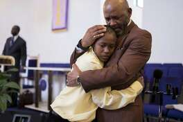Reverend Melvin Price, right, hugs Malcolm Harvin, 11, second right, during Sunday service at Dominion Church of God in Christ on Sunday, January 8, 2016 in San Antonio, Texas.