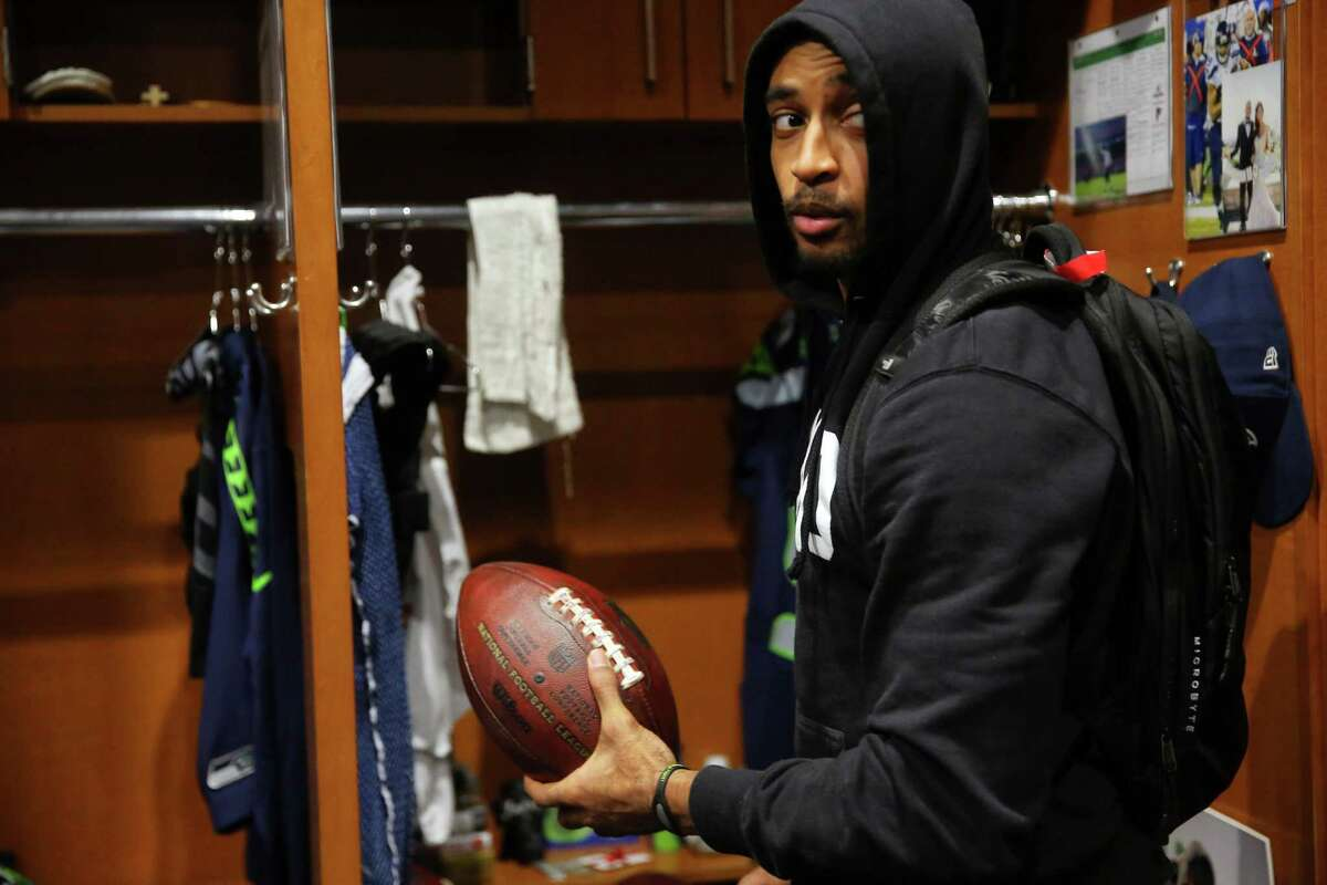 Seahawks wide receiver Doug Baldwin holds up the ball he used to throw his first touchdown pass this season as he and other players clean out their lockers the day after the Seahawks played their final game of the season against Atlanta, Sunday, Jan. 15, 2017 at Virginia Mason Athletic Complex.