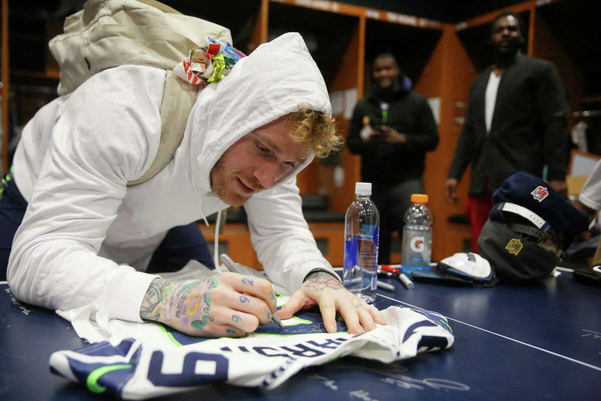 Seahawks defensive lineman Cassius Marsh signs a jersey for teammate Ronald Powell as players clean out their lockers the day after the Seahawks played their final game of the season against Atlanta, Sunday, Jan. 15, 2017 at Virginia Mason Athletic Complex.