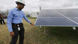 James Boston, manager of market intelligence for CPS Energy, shows the microgrid test site at Joint Base San Antonio-Fort Sam Houston, which includes three banks of solar panels and a 75-kilowatt battery that can provide power to the post's library.