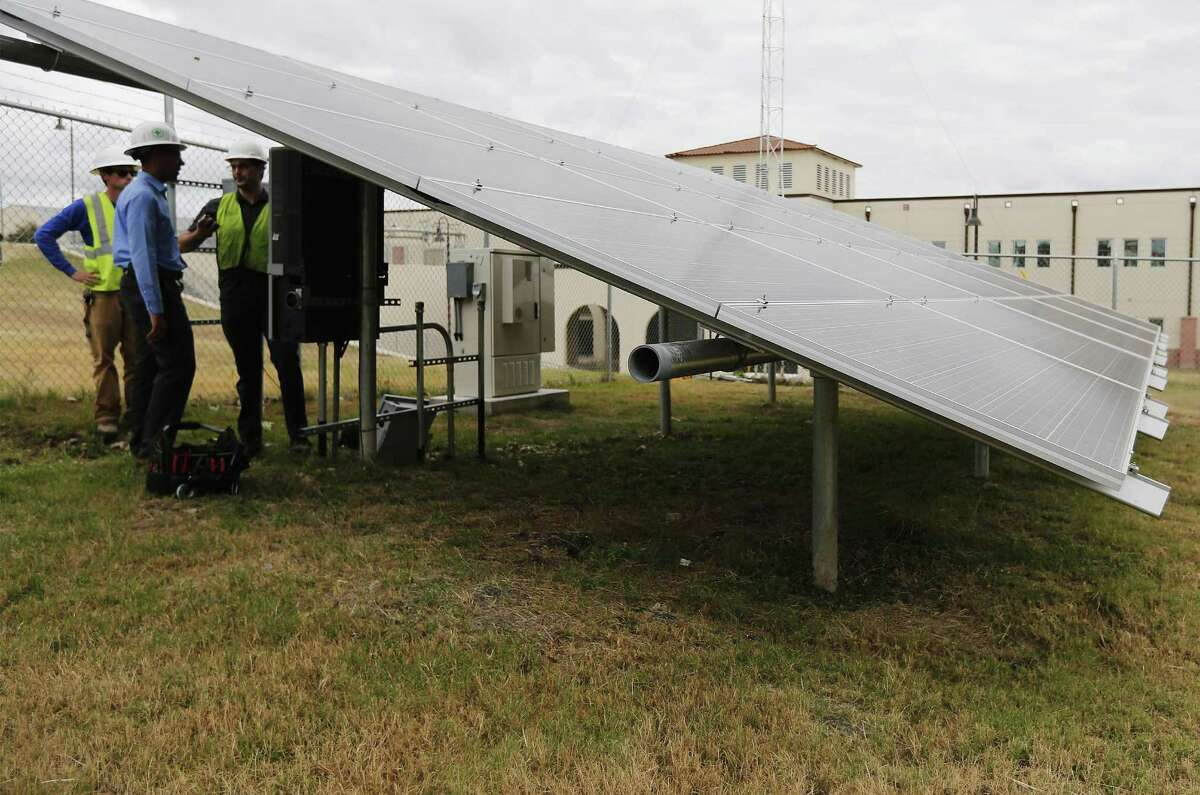 CPS Energy's James Boston, Manager of Market Intelligence, talks with contractors while they were upgrading inverters on a set of solar panels at the microgrid site built at JBSA-Fort Sam Houston on Friday, Jan. 13, 2017. The site consists of three banks of solar panels and a small facility which stores about 78-Kilowatts of Lithium-Ion batteries and a control station which can provide power to the post's library. The site is being used as a test bed for CPS Energy as well as for the Department of Defense to seek out solutions to gradually veer toward renewable energy options on military facilities. The site was funded by CPS Energy through a grant from the National Renewable Energy Labratory. The microgrid can wholly keep the library powered and off the CPS Energy grid for about 30 minutes from it's stored battery power according to officials. (Kin Man Hui/San Antonio Express-News)