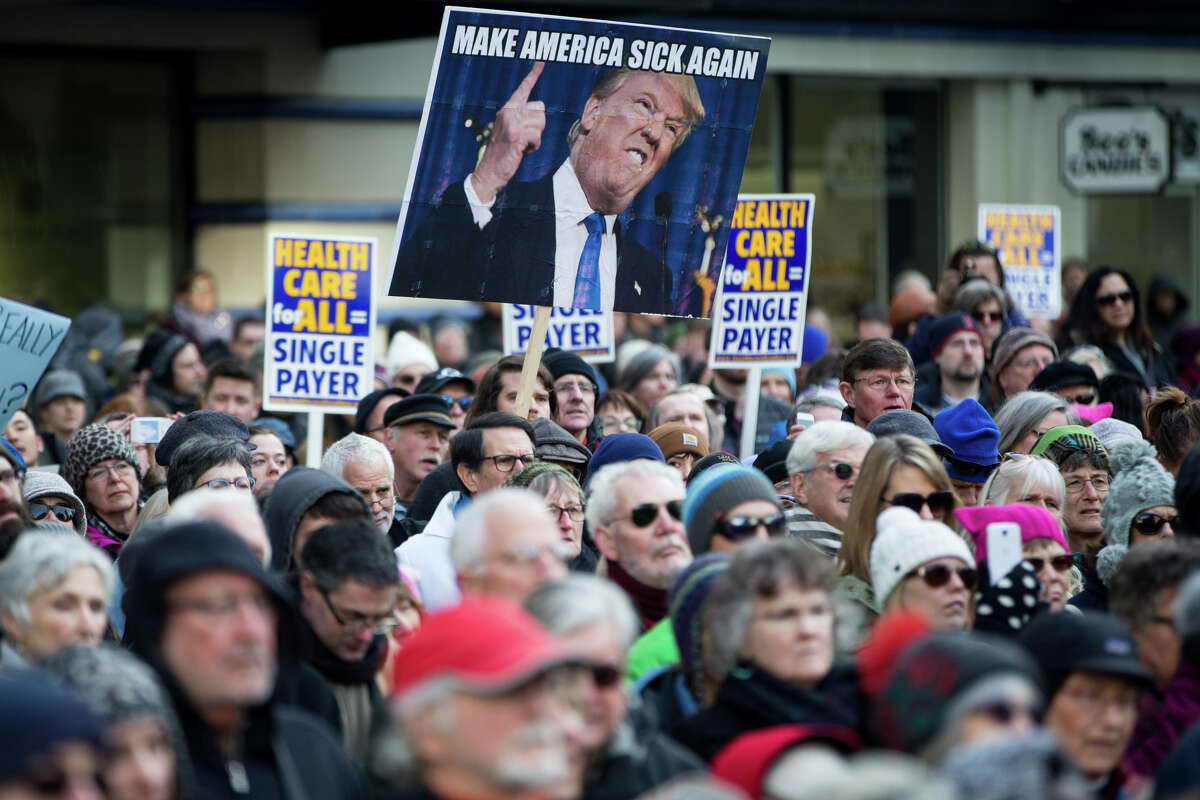 An anti-Trump sign sticks out from the crowd during a protest of the push by Republican-lead government towards defunding the Affordable Care Act, at Westlake Park on Sunday, Jan. 15, 2017. (GRANT HINDSLEY, seattlepi.com)