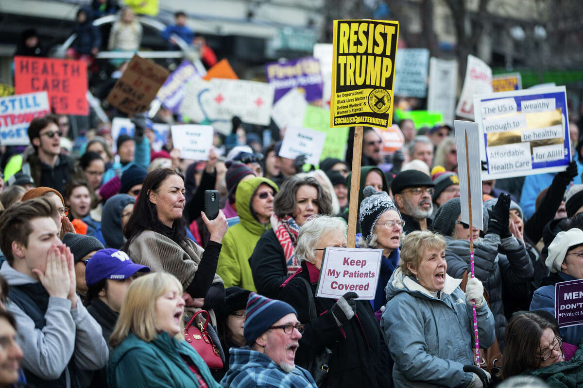 People gather to protest the push by Republican-lead government towards defunding the Affordable Care Act, at Westlake Park on Sunday, Jan. 15, 2017. (GRANT HINDSLEY, seattlepi.com)