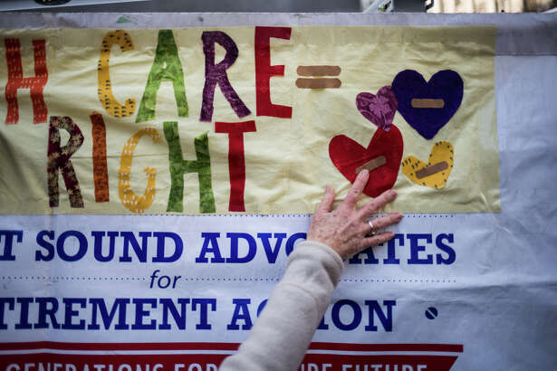 A woman puts a sign up during a protest the push by Republican-lead government towards defunding the Affordable Care Act, at Westlake Park on Sunday, Jan. 15, 2017. (GRANT HINDSLEY, seattlepi.com)