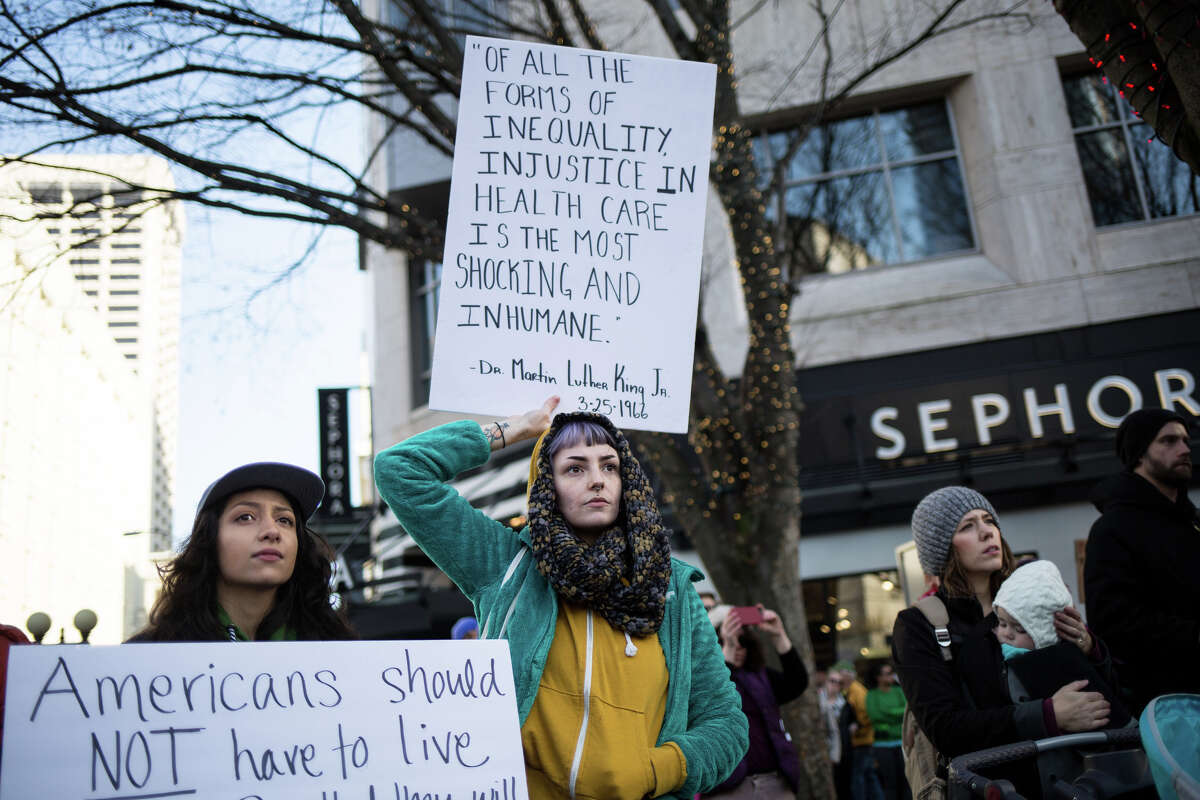 People gather to protest the push by Republican-led government towards defunding the Affordable Care Act, at a Westlake Park rally sponsored by Rep. Pramila Jayapal, five days before President Trump took office.