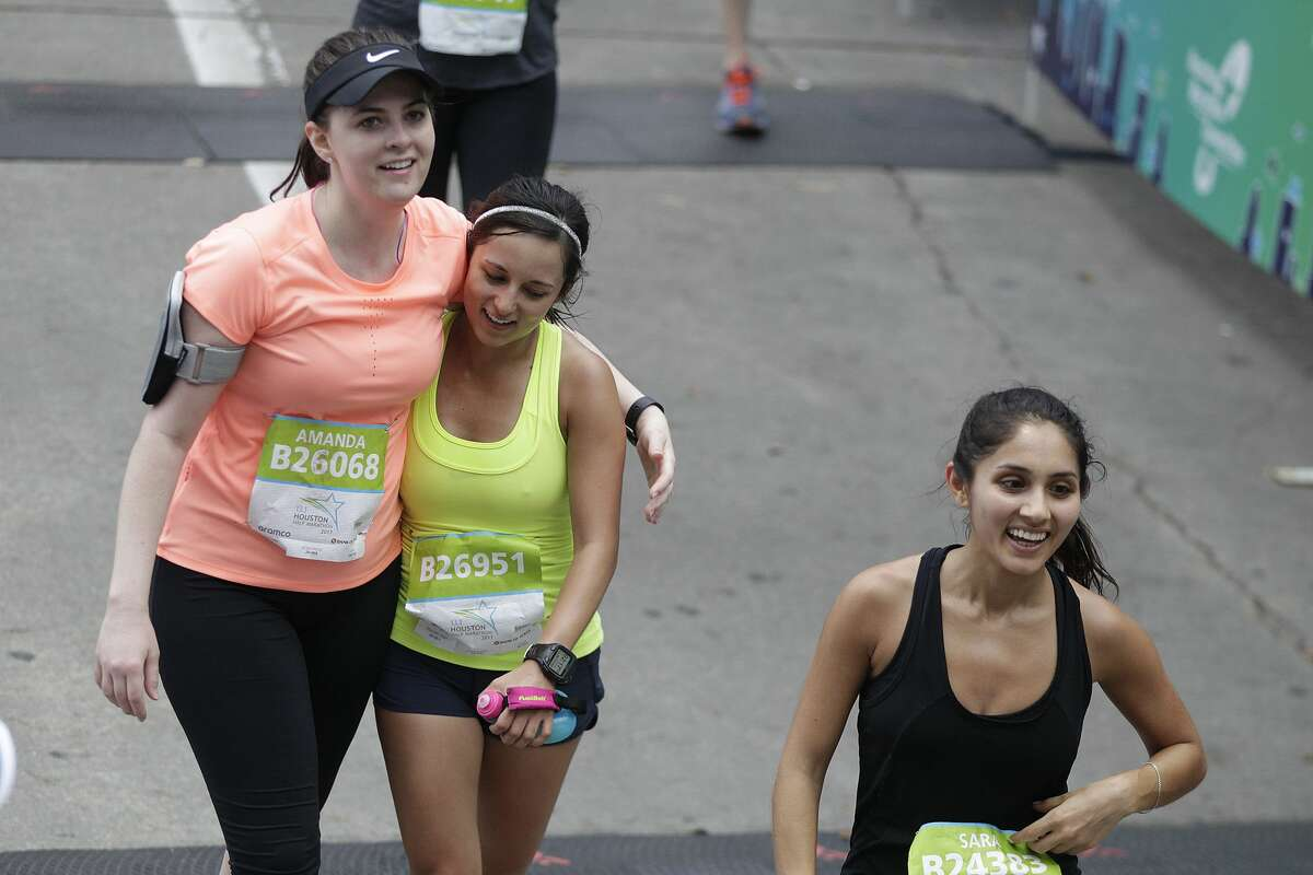 Runners smile as they cross the finish line during the Chevron Houston Marathon on Sunday, Jan. 15, 2017, in Houston. ( J. Patric Schneider / For the Chronicle )