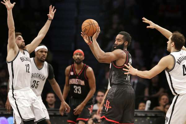 Houston Rockets' James Harden, second from right, passes through Brooklyn Nets defenders during the second half of the NBA basketball game at the Barclays Center, Sunday, Jan. 15, 2017 in New York. The Rockets defeated the Nets 137-112. (AP Photo/Seth Wenig)