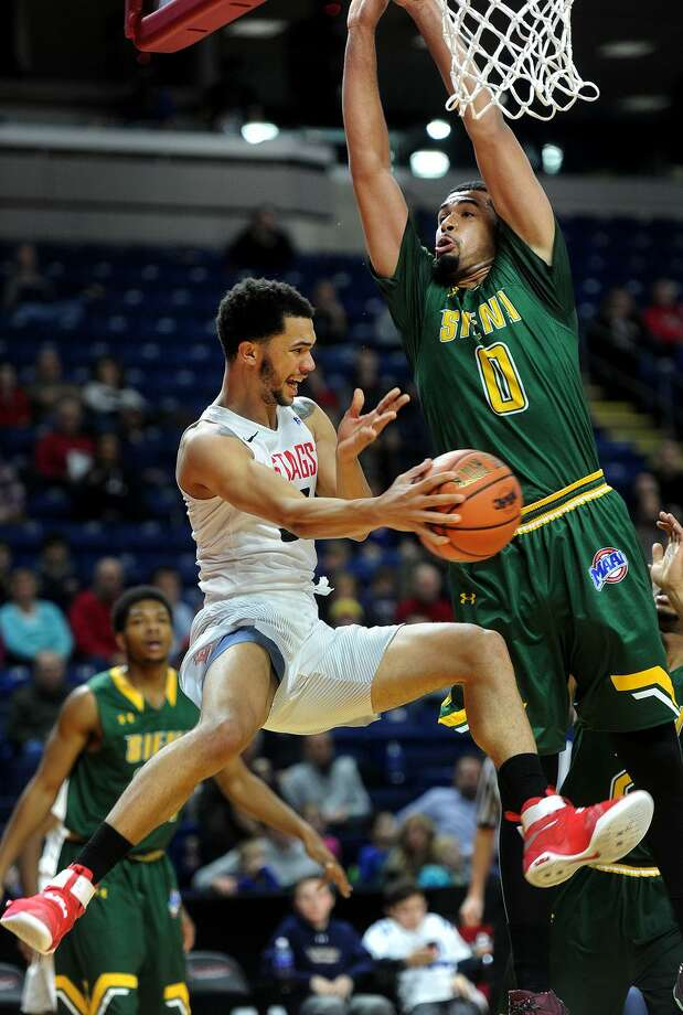Fairfiel's Curtis Cobb is forced to pass around Siena defender Javion Ogunyemi during the first half of Sunday's game at the Webster Bank Arena in Bridgeport. Photo: Brian A. Pounds / Hearst Connecticut Media / Connecticut Post