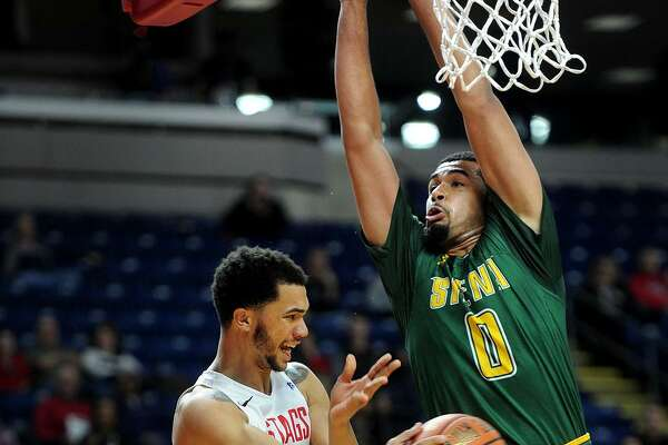 Fairfiel's Curtis Cobb is forced to pass around Siena defender Javion Ogunyemi during the first half of Sunday's game at the Webster Bank Arena in Bridgeport.