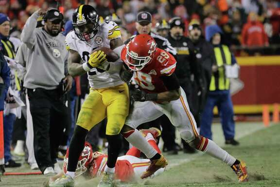 Pittsburgh Steelers running back Le'Veon Bell (26) is tackled by Kansas City Chiefs defensive back Daniel Sorensen (49 and strong safety Eric Berry (29) during the first half of an NFL divisional playoff football game Sunday, Jan. 15, 2017, in Kansas City, Mo. (AP Photo/Charlie Riedel)