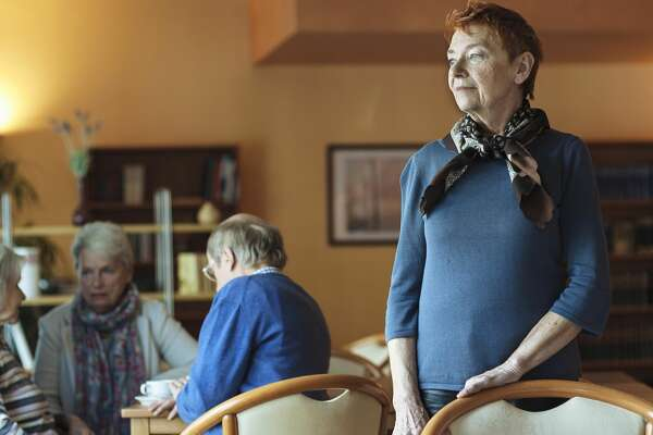 Senior Woman standing in retirement home.  Housemates in background.