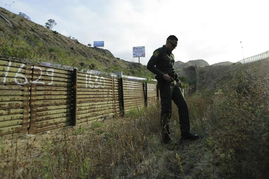 In this June 22, 2016 photo, a Border Patrol agent stands near a border structure in San Diego. Lawmakers, union leaders and polygraph experts contend that the use of lie detectors in the application process has gone awry and that many candidates are being subjected to unusually long and hostile interrogations, which some say can make people look deceptive even when they are telling the truth. (AP Photo/Gregory Bull) Photo: Gregory Bull, STF / Associated Press / Copyright 2017 The Associated Press. All rights reserved.