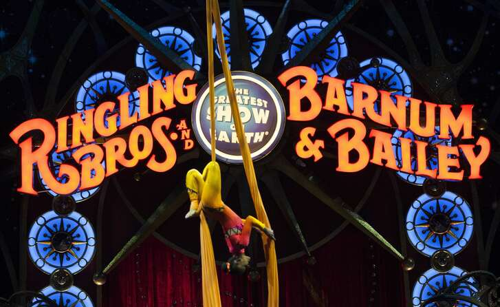 A circus performer hangs upside down during a Ringling Bros. and Barnum & Bailey Circus performance in Washington, DC on March 19, 2015. Across America through the decades, children of all ages delighted in the arrival of the circus, with its retinue of clowns, acrobats and, most especially, elephants. But, bowing to criticism from animal rights groups, the Ringling Bros. and Barnum & Bailey Circus announced on March 5, 2015, it will phase out use of their emblematic Indian stars. (Photo credit should read Andrew Caballero-Reynolds/AFP/Getty Images)