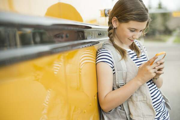 Schoolgirl leaning on school bus while using smart phone