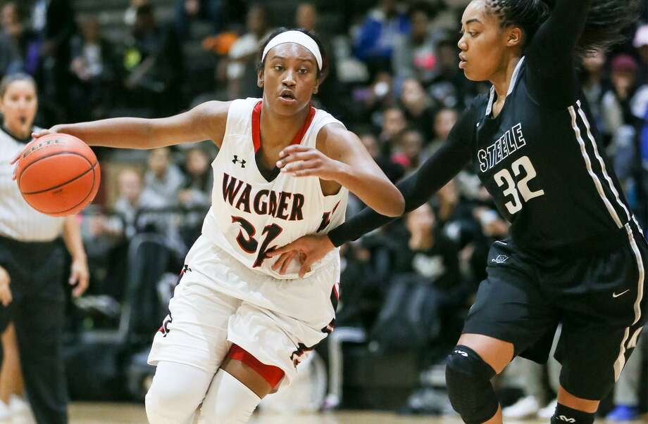 Wagner's Da'Nasia Hood (left) drives into the lane around Steele's Antonia Anderson during a District 27-6A girls basketball game at Wagner on Dec. 16, 2016. Photo: Marvin Pfeiffer /San Antonio Express-News / Express-News 2016
