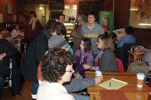 Illinois' 112th District State Representative Katie Stuart, seated in gray, listens to a constituent Saturday morning during her first Coffee with Katie community meeting. The Edwardsville Democrat, who was sworn into the state legislature last week, greeted area residents at Sacred Grounds Cafe on North Main Street. Stuart will conduct other Coffee with Katie events later in her district.