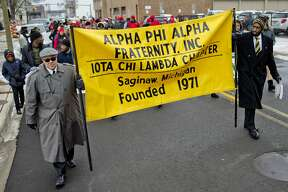 """Iota Chi Lambda Chapter of Alpha Phi Alpha Fraternity, Inc., members Maurice Potts, left, and Julius Boarden Jr., right, hold a banner and march with other organizations and community members along Franklin Street on their way to The Dow Event Center during the 20th Annual Dr. Martin Luther King Jr. Unity March and Luncheon on Monday in Saginaw. Marchers walked a route beginning at Franklin and Hayden streets and ending at The Dow Event Center. The group sang """"We shall overcome"""" during the march. The luncheon began  at 11 a.m. and featured a keynote speech from U.S. Rep. Dan Kildee of  Michigan's 5th District. The event was held on Martin Luther King Jr.  Day to honor and celebrate the life and legacy of the civil rights  activist. Iota Chi Lambda Chapter of Alpha Phi Alpha Fraternity, Inc.,  and the Delta College Black Faculty and Staff hosted the event."""