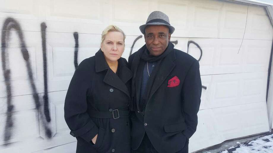 Heather Lindsay and her common-law husband Lexene Charles in front of the garage door of their Bull's Head residence that was vandalized with a racial slur sometime early Saturday morning in Stamford. Photo: John Nickerson / Hearst Connecticut Media