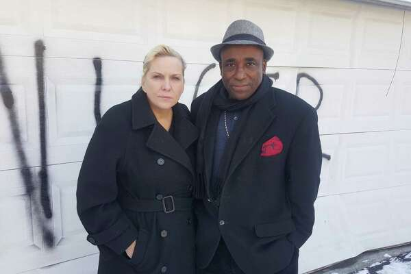Heather Lindsay and her common-law husband Lexene Charles in front of the garage door of their Bull's Head residence that was vandalized with a racial slur sometime early Saturday morning in Stamford.