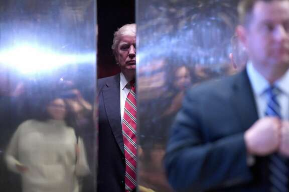 U.S. President-elect Donald Trump, center, waits in an elevator in the lobby of Trump Tower in New York, U.S., on Monday, Jan. 16, 2017. President-elect Donald Trump's pledge to cancel the executive orders of his predecessor would have wide-ranging implications in compensation, paid leave, diversity in hiring, and protection for gay and transgender employees in the workplace. Photographer: Anthony Behar/Pool via Bloomberg