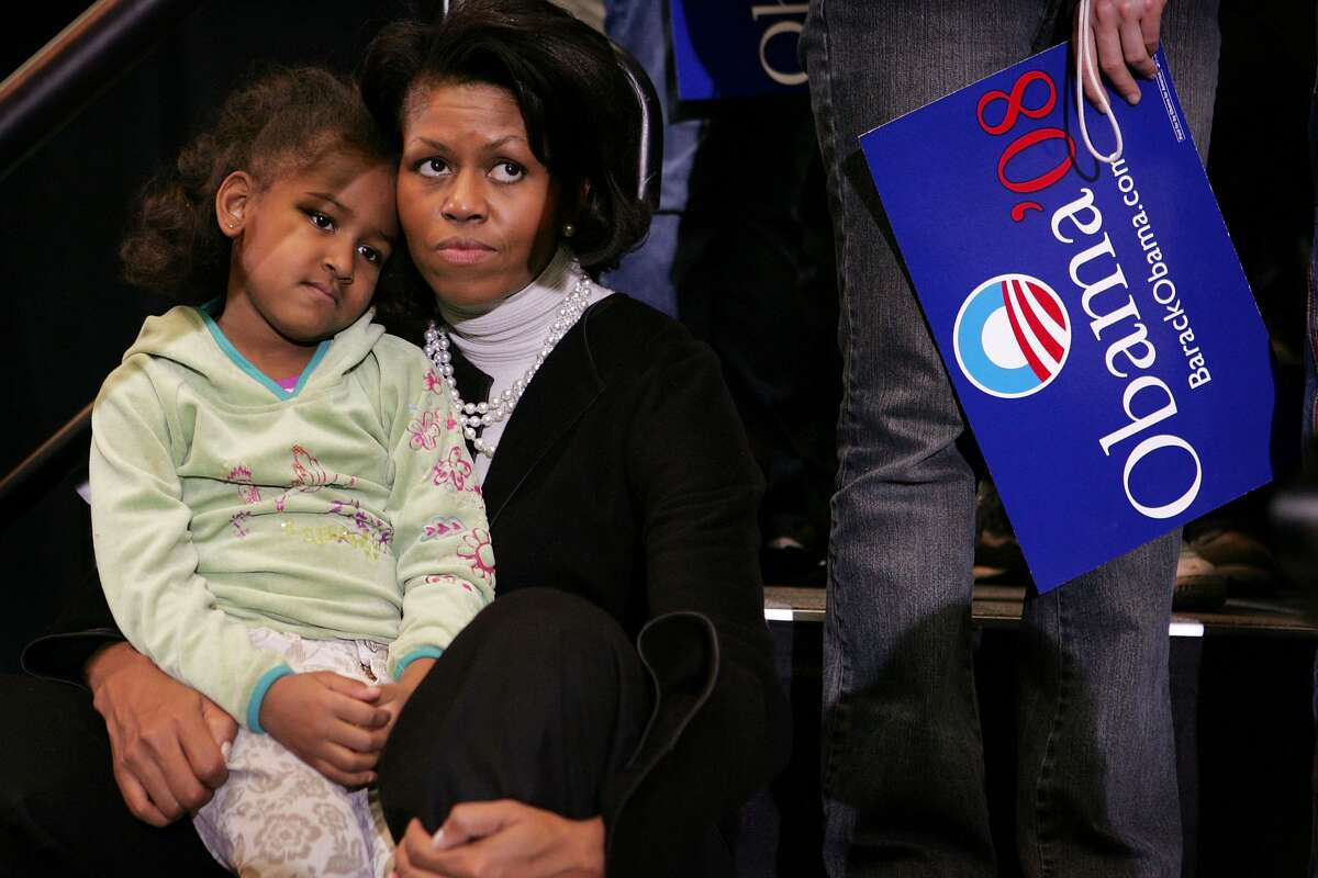 Michelle Obama, wife of Senator Barack Obama (D-IL), listens with her daughter Sasha as the Senator addresses a crowd gathered at a campaign rally at Iowa State University February 11, 2007 in Ames, Iowa. Obama is wrapping up a two-day campaign swing through Iowa after announcing February 10, that he would seek the Democratic nomination for President.