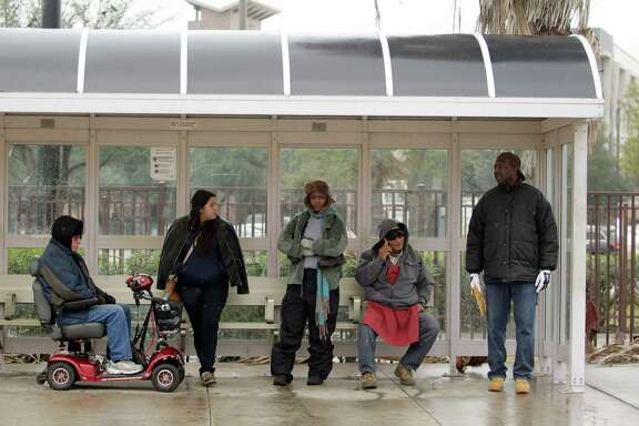 Metro users attempt to stay warm while waiting for a bus at the Wheeler station on Friday, Jan. 6, 2017, in Houston.