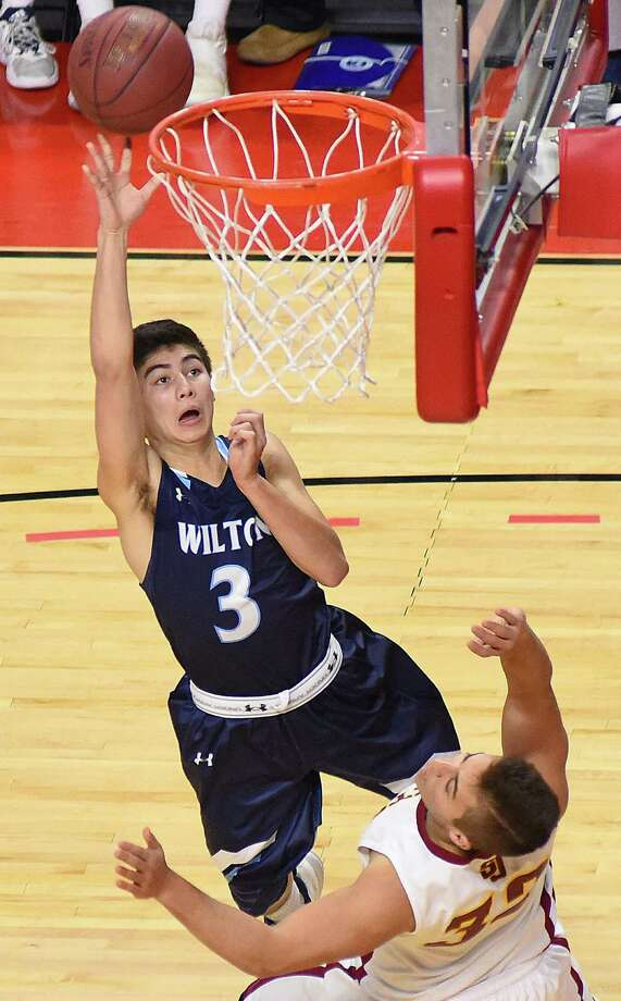 Wilton's Matt Kronenberg (3) runs over St. Jospeh's Alec Pelletier for a player control foul during the third quarter of Monday's matinee FCIAC boys basketball game at Webster Bank Arena in Bridgeport. Wilton edged St. Joseph 62-61 in the opening game of the MLK/Ali Classic basketball showcase. Photo: John Nash / Hearst Connecticut Media / Norwalk Hour