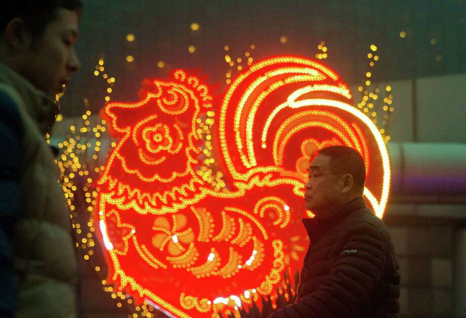 Men walk past neon decorations marking the Year of the Rooster in Beijing, China, Monday, Jan. 16, 2017. The Lunar New Year which falls on Jan. 28 this year marks the Year of the Rooster in the Chinese calendar. Photo: Ng Han Guan, Associated Press / Copyright 2017 The Associated Press. All rights reserved.