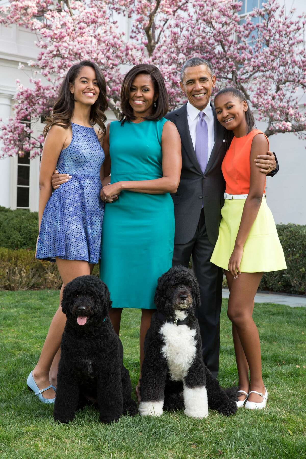 President Barack Obama, First Lady Michelle Obama, and daughters Malia (L) and Sasha (R) pose for a family portrait with their pets Bo and Sunny in the Rose Garden of the White House on Easter Sunday, April 5, 2015 in Washington, DC.