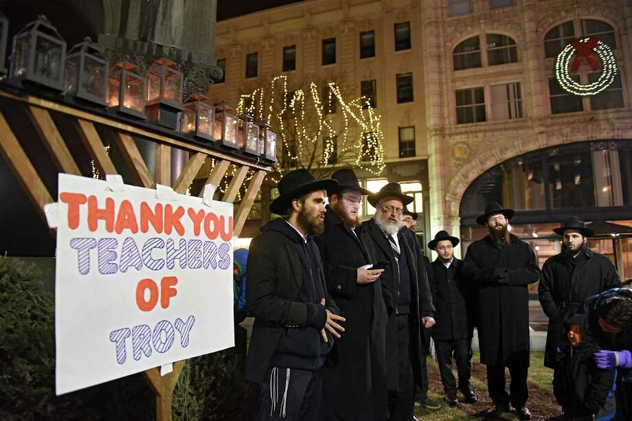 From left, Yehoshua Carbonera of St. Paul, MN, Shlomo Morrison, Rabbi Leible Morrison of Beth Tephilah Synagogue and others sing a song after lighting the third candle in a menorah as the city of Troy celebrates Hanukkah with a menorah lighting ceremony at Monument Square on Wednesday, Dec. 28, 2016 in Troy, N.Y. Each night the city thanks a different group of people. Tonight they were thanking teachers. (Lori Van Buren / Times Union) Photo: Lori Van Buren / 20039253A