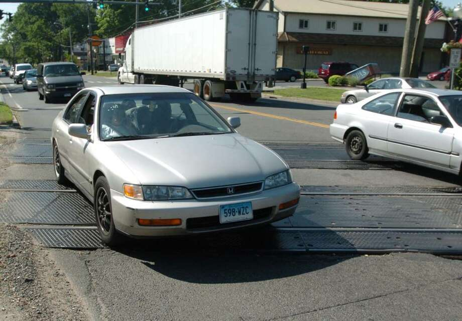Cars slowly approach broken train tracks on Main Street in Danbury, Wednesday, May 26, 2010. Photo: Chris Ware / The News-Times