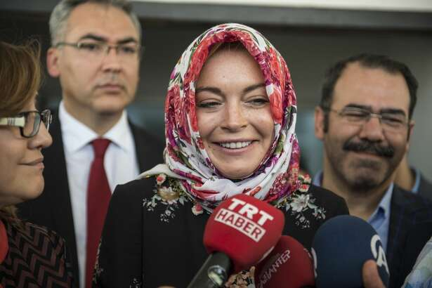 American actress Lindsay Lohan (C) speaks to press members with wearing a headscarf given by a Syrian woman, after her visit at a container town where Syrian refugees live in the Nizip district of Gaziantep in Turkey on October 08, 2016.