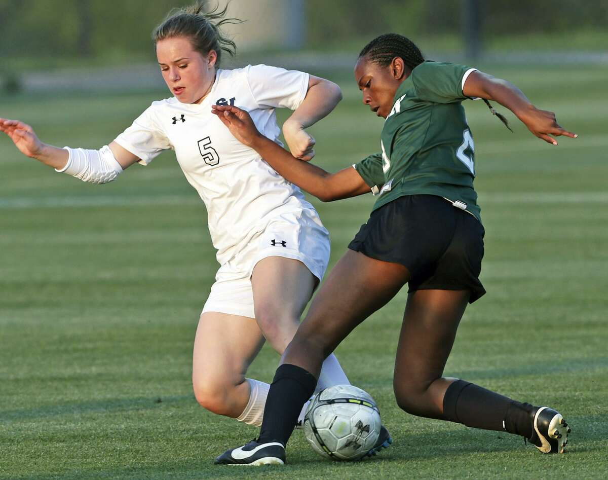 The Rangers' Allee Schroeder (5) and the Rattlers' Tyanne Pearcy battle as the Reagan girls beat Smithson Valley 1-0 in third round 6A soccer playoffs at the UTSA Park West Complex on April 7, 2015.