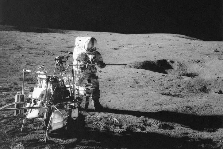 FILE - In this Feb. 13, 1971 file photo, Apollo 14 astronaut Alan B. Shepard Jr. conducts an experiment near a lunar crater, using an instrument from a two-wheeled cart carrying various tools. On Wednesday, Jan. 11, 2017, a California-led research team reported that the moon formed within 60 million years of the birth of the solar system. Previous estimates ranged within 100 million years, all the way out to 200 million years of the solar system�s creation. (NASA via AP)